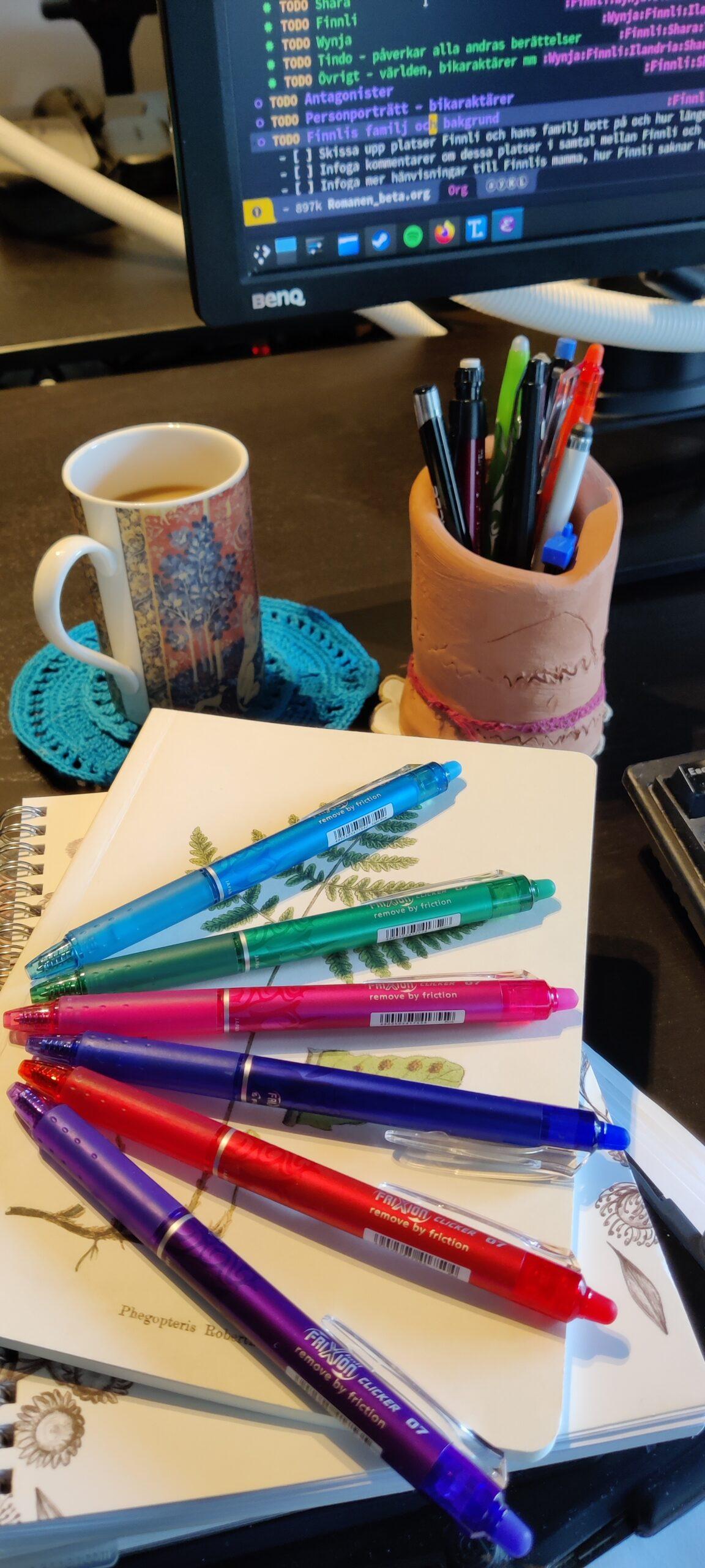Skrivplats med dator, pennor och anteckningsblock.